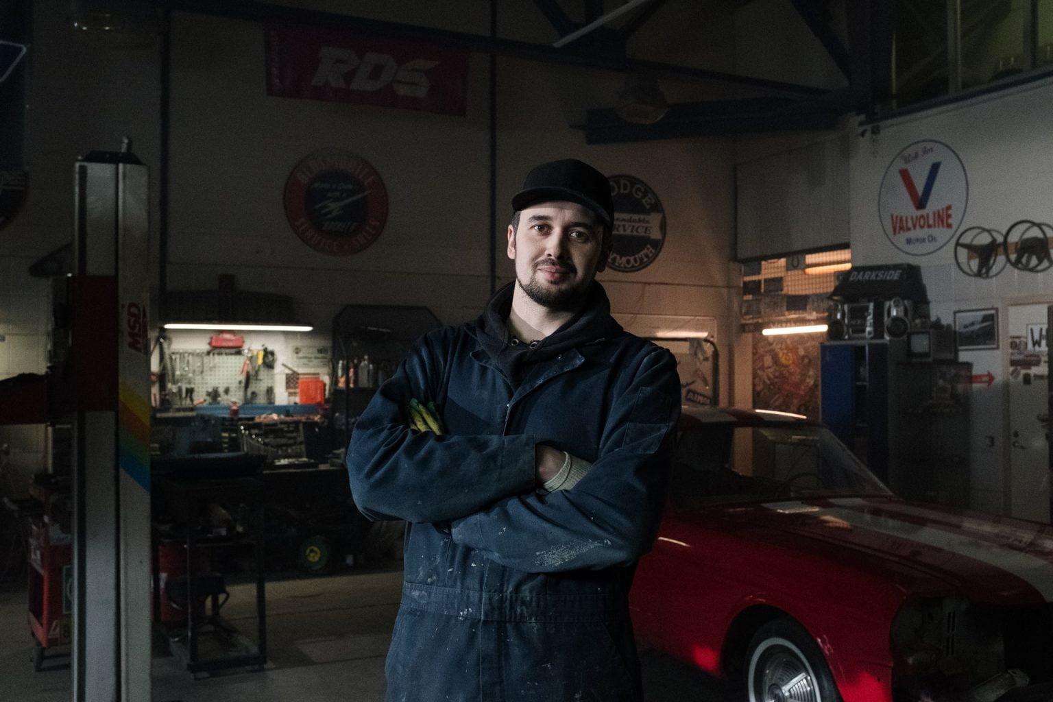 Man in een garage met zijn armen over elkaar heen